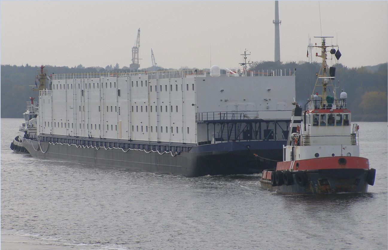 accommodation barge being towed by tug